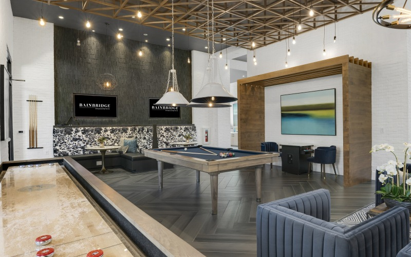 billiards and shuffle board table in well lit game room